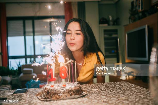 teenager latina blowing out candles in her birthday at homeowing out candles on a birthday cake - archival stock pictures, royalty-free photos & images