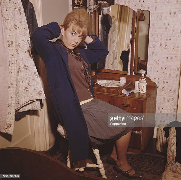 Teenager Laureen Jones adjusts her beehive hairstyle at a dressing table in a bedroom in England in 1962
