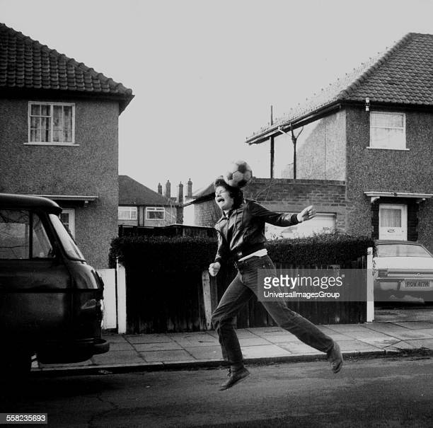 Teenager leaps for a ball in a suburban street in 1979