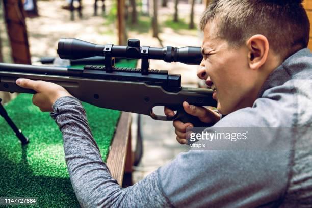 teenager learning how to use a rifle - objetivo militar imagens e fotografias de stock