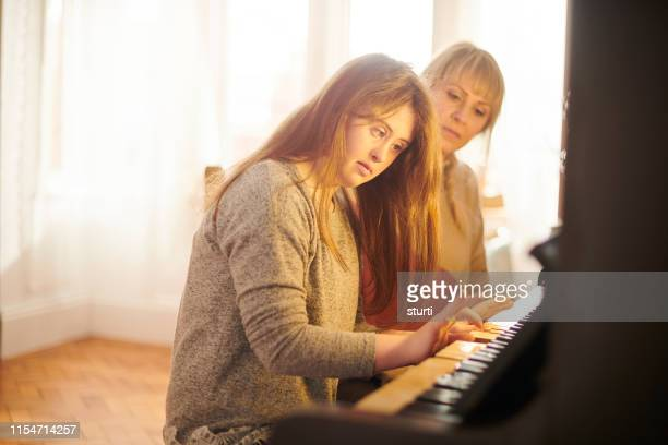 teenager learning piano - learning disability stock pictures, royalty-free photos & images