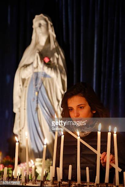 Teenager lighting a candle in La Madeleine church