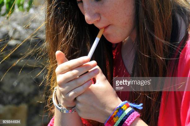 Teenager lighting up a cigarette