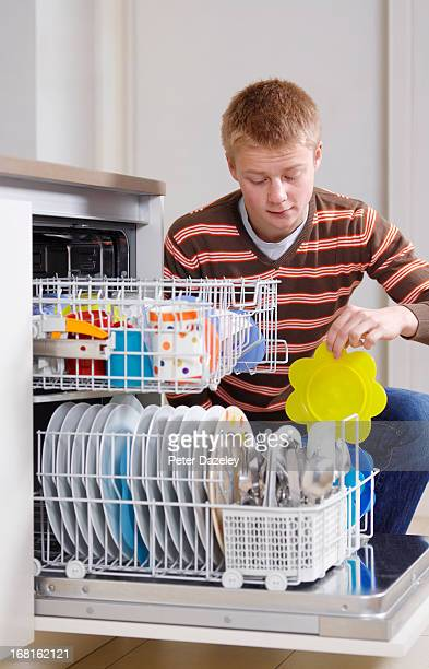 teenager loading dishwasher - chores stock pictures, royalty-free photos & images