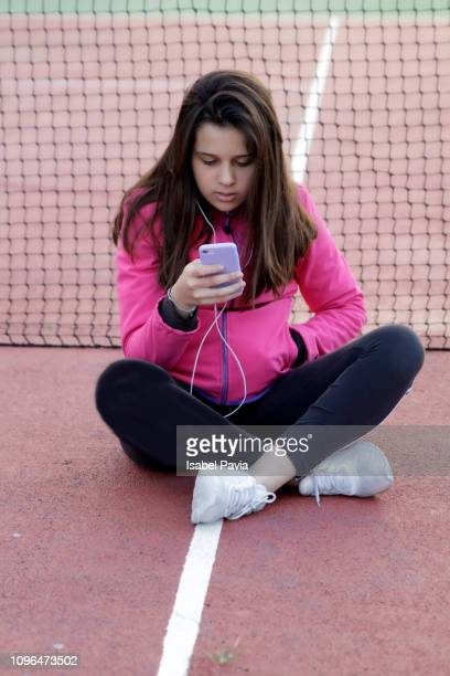 Teenager looking at cell phone before exercising