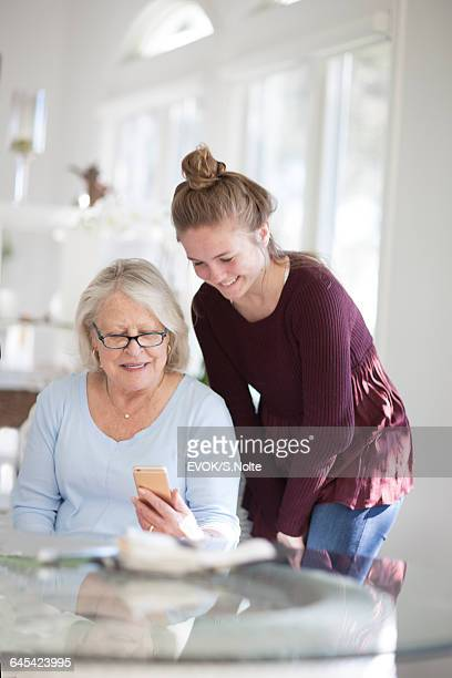 Teenager Looking at Smart Phone with Grandmother
