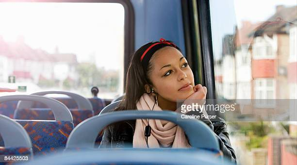 Teenager looking out of window on top deck of bus