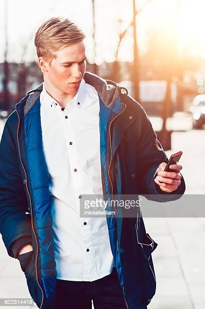Teenager looks smart phone while walking outside