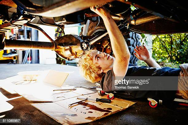 Teenager lying on driveway replacing oil pan