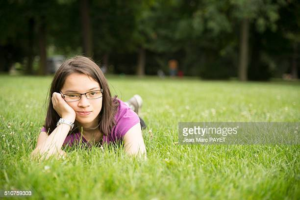 teenager lying on grass - jean marc payet stockfoto's en -beelden