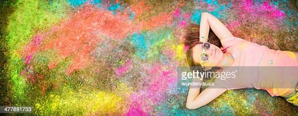 Teenager lying on holi powder covered festival ground