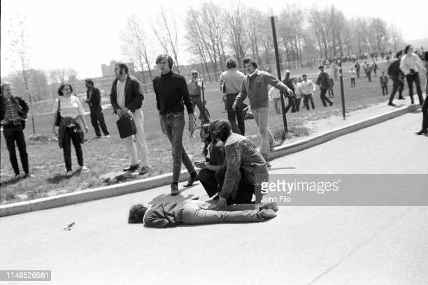 Teenager Mary Ann Vecchio and another unidentified person kneel over the body of Kent State University student Jeffrey Miller who had been shot...