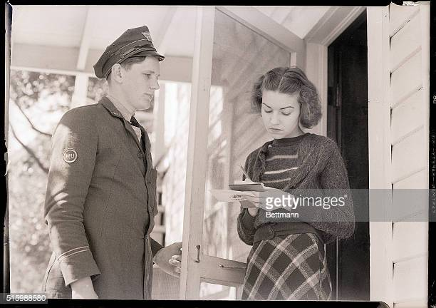 Teenager Maxine Maddox signs for a telegram that Western Union messenger Stanley G Roseboom has delivered to her door Photo circa 1950
