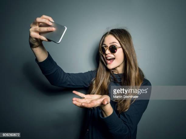 teenager mädchen macht selfies mit handy - stralende lach stockfoto's en -beelden