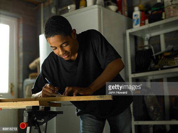 Teenager measuring wood