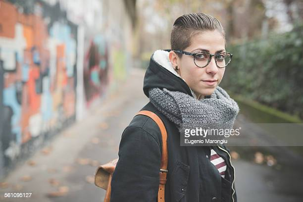 Teenager on street, graffiti wall in background