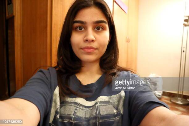 a teenager pakistani girl smiling and making selfie - selbstportrait stock-fotos und bilder