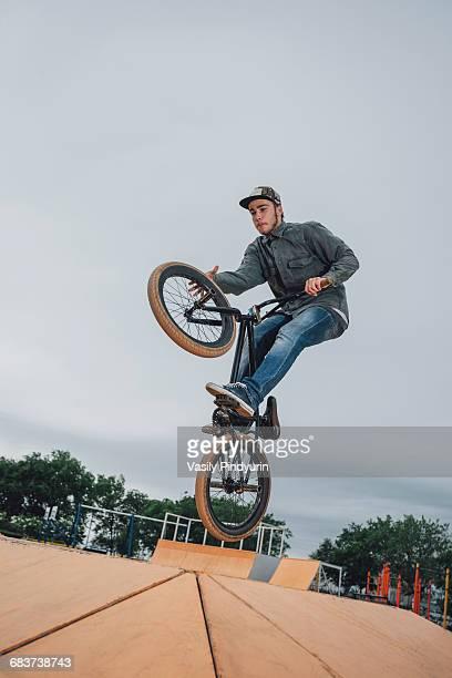 Teenager performing stunt at skateboard park against sky