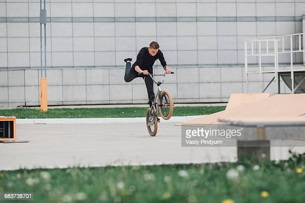Teenager performing wheelie with bicycle at skateboard park