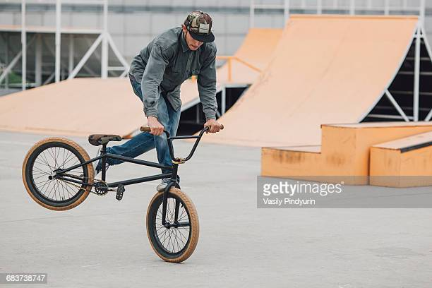 teenager performing wheelie with bicycle at skateboard park - bmx cycling stock pictures, royalty-free photos & images
