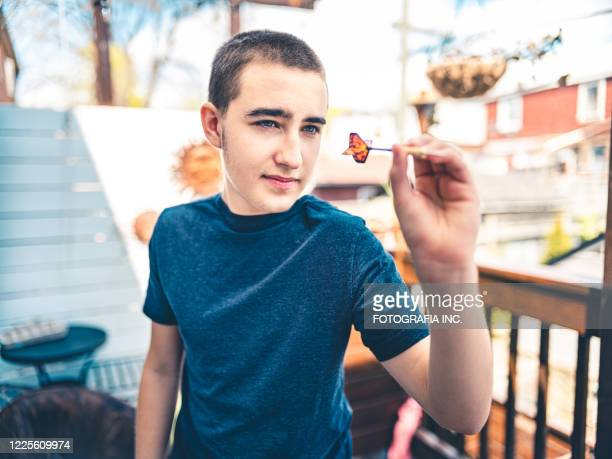 teenager playing darts outside - darts stock pictures, royalty-free photos & images