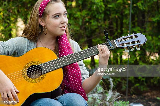 Teenager playing guitar and singing in the garden.