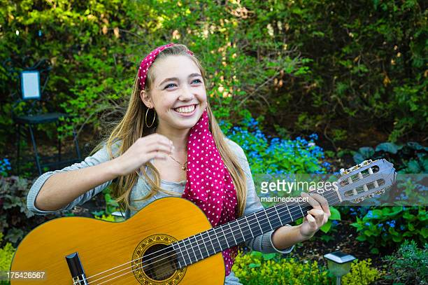 "teenager playing guitar and singing in the garden. - ""martine doucet"" or martinedoucet stockfoto's en -beelden"