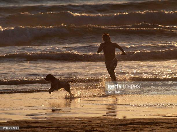 Teenager playing insea with his dog at sunset