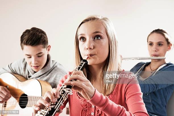teenager playing music - oboe stock-fotos und bilder