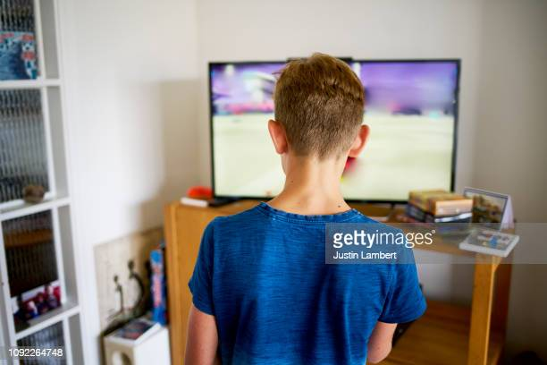 teenager playing video games in the living room viewed from the back - saltdean stock pictures, royalty-free photos & images