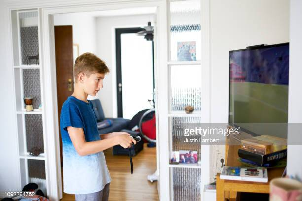 teenager playing video games on the living room television - saltdean stock pictures, royalty-free photos & images