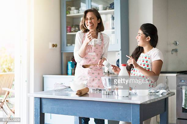 Teenager playing with mother while cooking at home