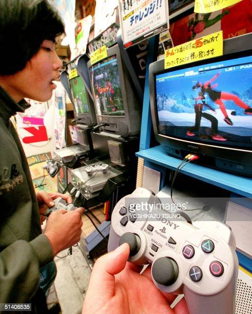 Teenager plays a video game on Sony's Playstation machine at a computer shop in Tokyo's Akihabara electronic shops district 08 May. Japanese...