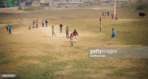 Teenager poor kids playing cricket in Open Ground During Afternoon.