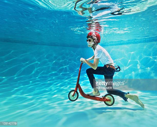 teenager pushing a scooter underwater - bizarre stock pictures, royalty-free photos & images