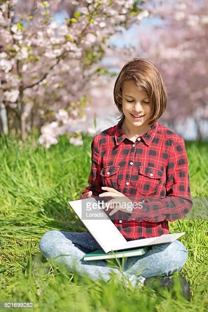 teenager reading books in cherry blossom garden