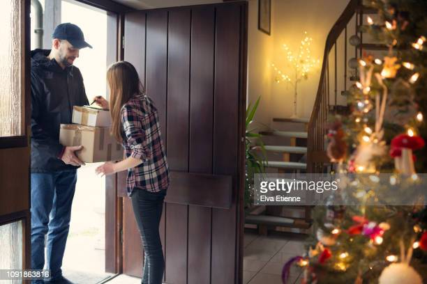 teenager receiving christmas packages delivered by postman - open source stock pictures, royalty-free photos & images