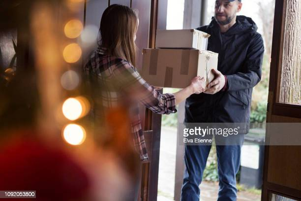 teenager receiving christmas packages delivered by postman - receiving stock pictures, royalty-free photos & images