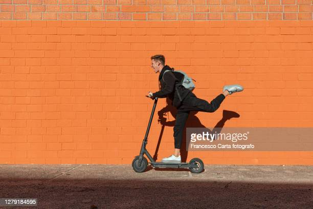teenager riding electric scooter - freedom stock pictures, royalty-free photos & images