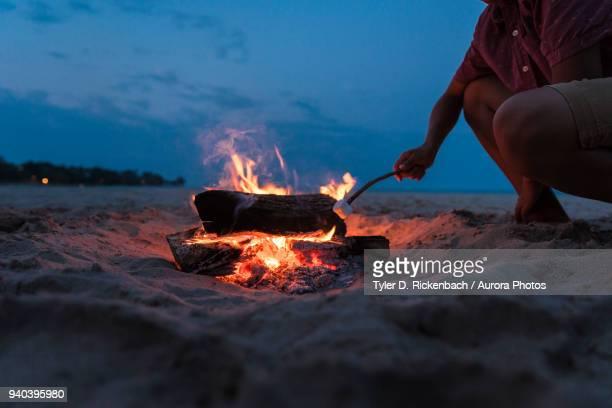 teenager roasting marsh mellow on beach while kneeling next to small fire in sand, sheboygan, wisconsin, usa - ウィスコンシン州シボイガン ストックフォトと画像