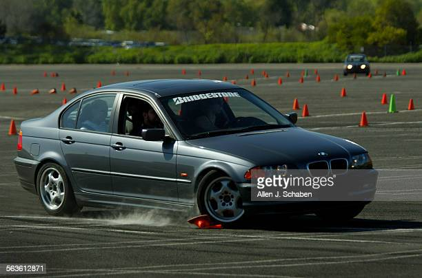 A teenager runs over a cone during a braking exercise on a curved course of Driver's Edge a nonprofit youth driver education program founded by...