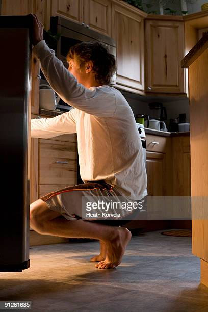 Teenager searching in refrigerator for snack.