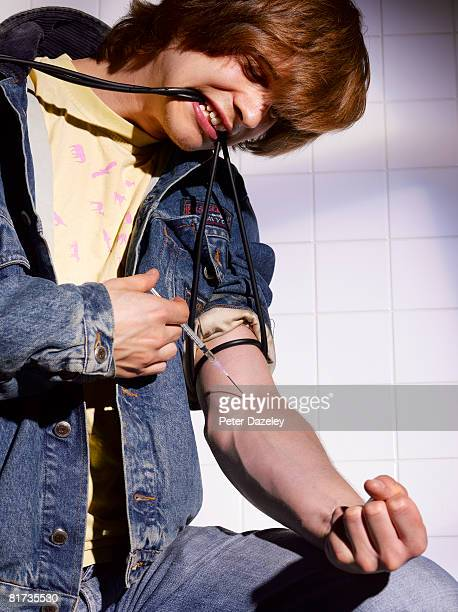 teenager shooting heroin in bathroom. - heroin addict arm stock photos and pictures