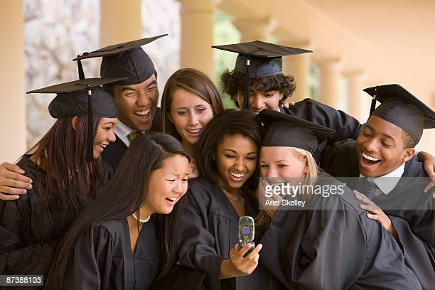 Teenager showing fellow graduates picture on cell phone