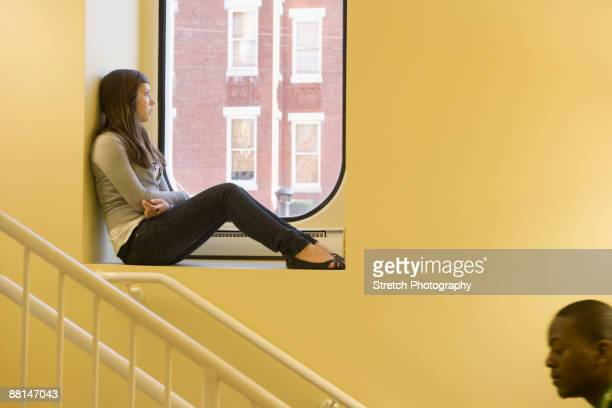 teenager sitting in window sill - good; times bad times stock pictures, royalty-free photos & images