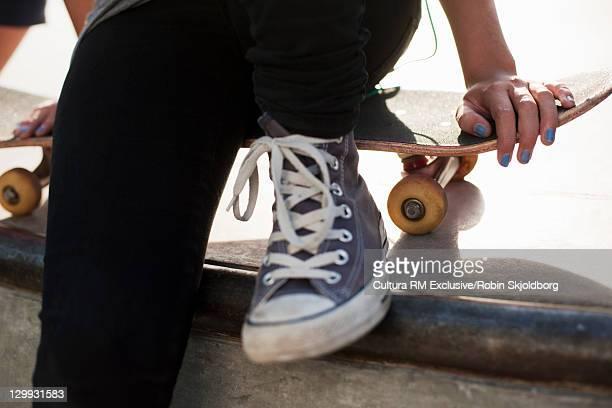 Teenager sitting on skateboard