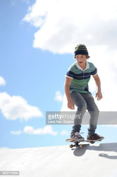 teenager skateboarding on skateboard against sky - lene pels stockfoto's en -beelden