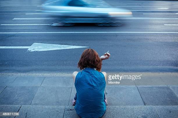 Adolescente fumare su un marciapiede