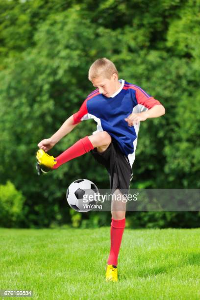 Teenager Soccer Boy Practicing and Kicking a soccer Ball on a Grass Lawn
