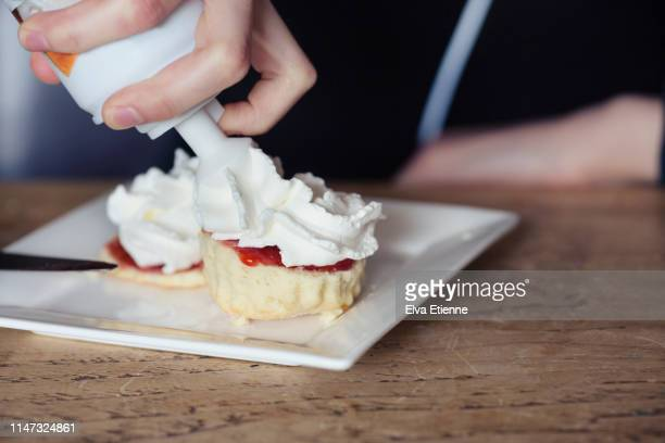 teenager squirting whipped cream from a can onto freshly baked scones - whipped food stock pictures, royalty-free photos & images